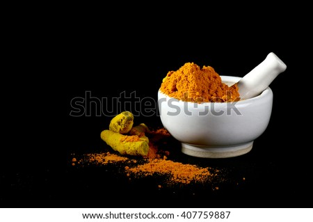 Turmeric powder in mortar with pestle and roots or barks on black background - stock photo