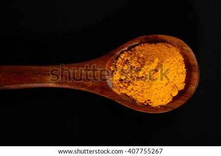 Turmeric powder in spoon on black background - stock photo
