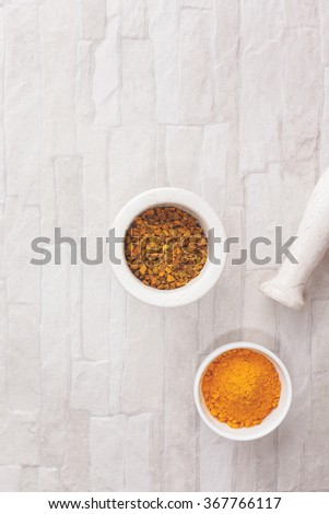 Turmeric spice in mortar and ceramics bowl.Turmeric spice in and beside a mortar. Top view, blank space, vintage toned image. Natural light - stock photo