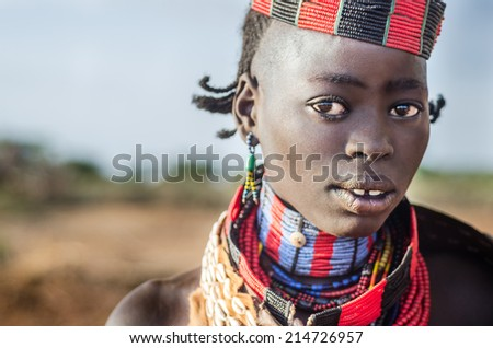 TURMI, ETHIOPIA - 12 AUGUST: portrait of unidentified Hamer tribe woman, Omo valley, 12 august 2014. Hamer woman usually comb their hairs with soil and wear many colored necklace - stock photo