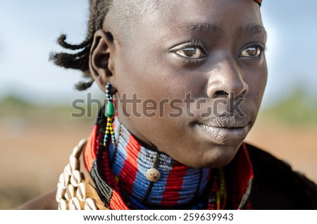 TURMI, ETHIOPIA - 12 AUGUST: portrait of unidentified Hamer tribe woman, Omo valley, 12 august 2014. Hamer woman usualy comb their hairs with soil and wear many colored necklace - stock photo
