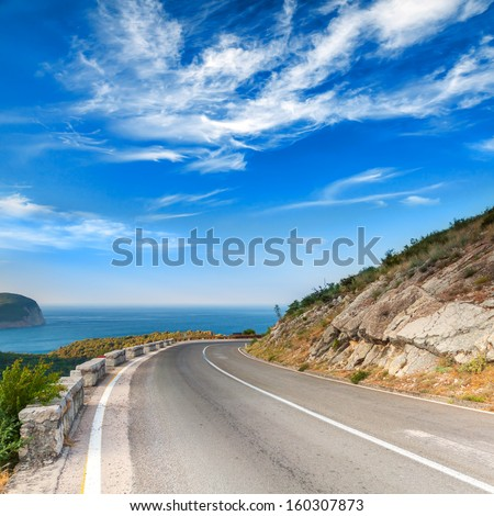 Turn of mountain highway with dramatic blue sky and sea on a background - stock photo