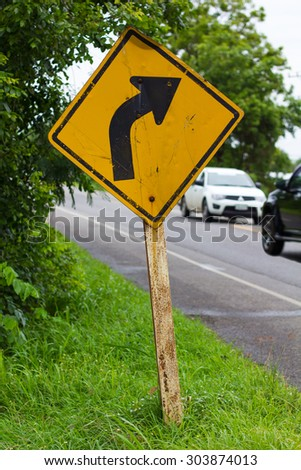 Turn right at the signpost old poles leaning on rural roads with cars passing traffic flow. - stock photo
