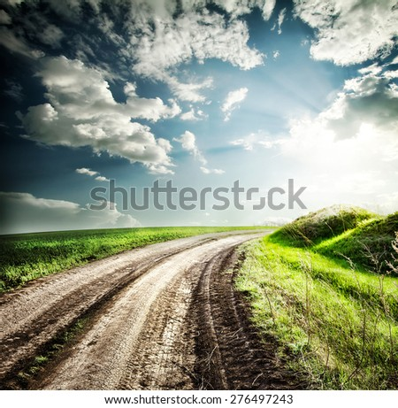 Turning highway into the field for hills under dramatic sky - stock photo
