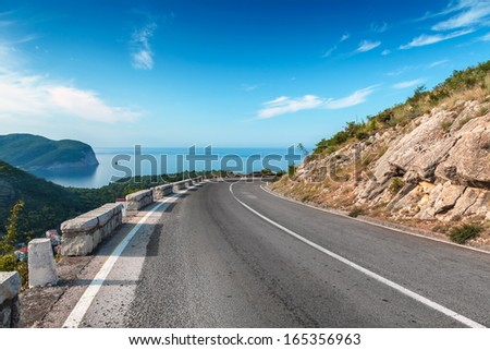Turning mountain highway with blue sky and sea on a background - stock photo