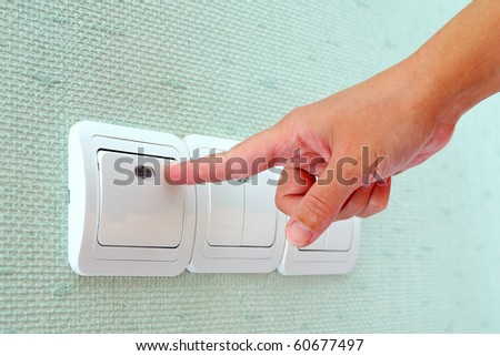 Turning off or turning on the wall-mounted light switch - stock photo