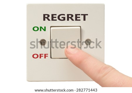 Turning off Regret with finger on electrical switch - stock photo