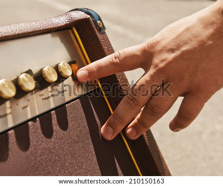 turning on guitar amplifier with hand finger - stock photo