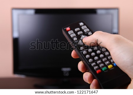 Turning on tv with remote control - stock photo