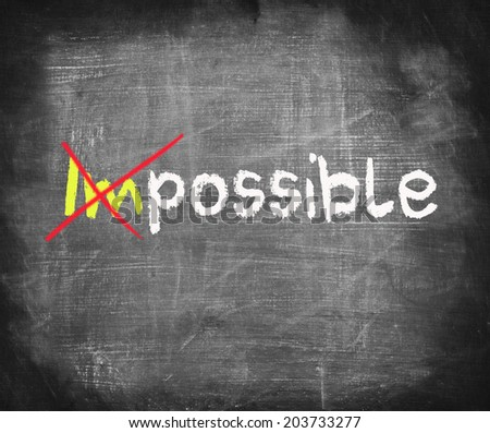 Turning the word Impossible into Possible with red chalk on blackboard - stock photo
