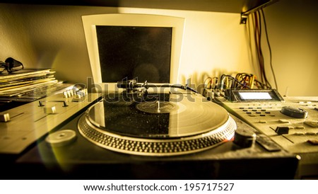 Turntable in home recording studio illuminated by a yellow light  - stock photo