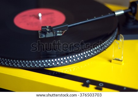 Turntable in yellow case playing a vinyl record with red label. Side view closeup - stock photo