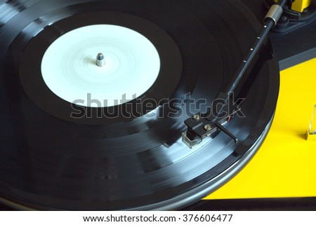 Turntable in yellow case playing a vinyl record with white label. Horizontal photo top view closeup - stock photo