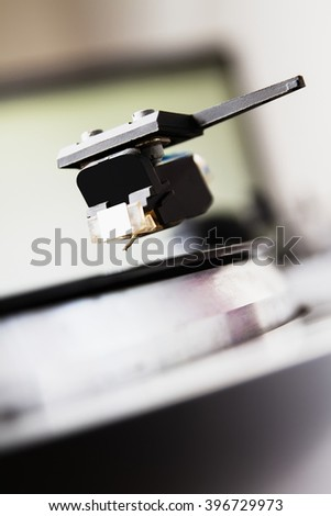 Turntable player with musical vinyl record. Useful for DJ, nightclub and retro theme. Focus on the needle, vertical orientation - stock photo