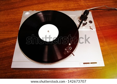 Turntable player with musical vinyl record. Useful for DJ, nightclub and retro theme, great for hipster theme. - stock photo