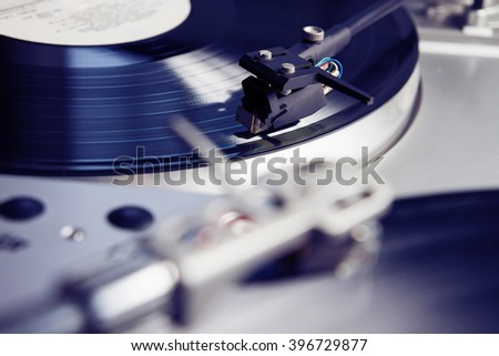 Turntable player with musical vinyl record. Useful for DJ, nightclub and retro theme. Violet color - stock photo