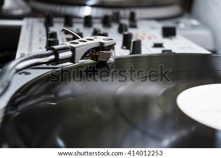 Turntable playing analog audio vinyl disc with music. Close up on record, tonearm and needle, macro photo. Professional audio equipment for DJ, nightclub or audio enthusiast.  - stock photo
