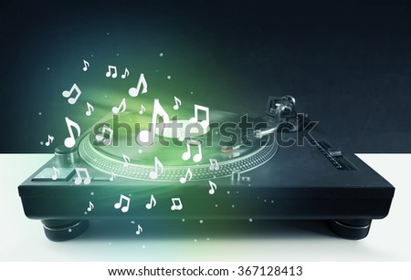 Turntable playing music with audio notes glowing concept on background - stock photo