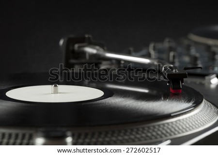 Turntable playing vinyl close up with needle on the record with grey background - stock photo