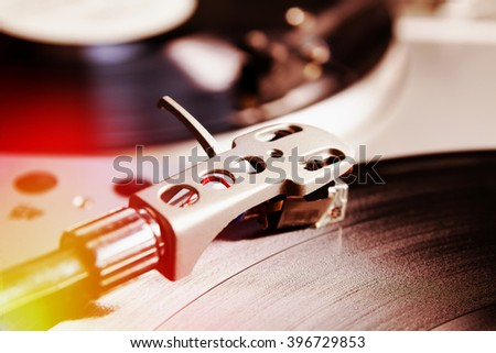 Turntable playing vinyl record with music. Useful equipment for DJ, nightclub and retro hipster theme or audio enthusiast. Light leak film hipster instagram filter effect - stock photo