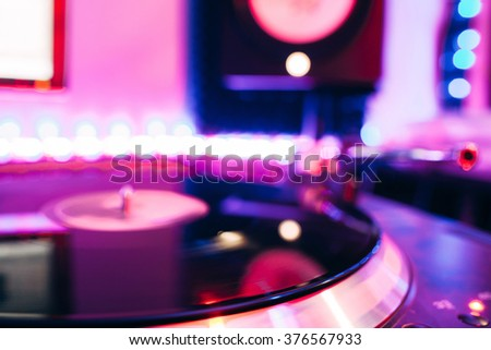 Turntable playing vinyl with club lighting - stock photo