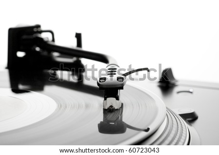 Turntable with spinning record, focus on stylus - stock photo