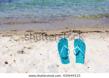 Turquoise blue flip flops on the beach along the Aegean sea, Greece - stock photo