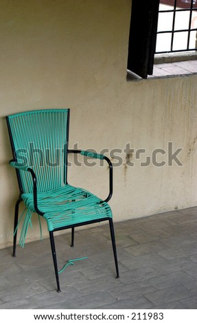 Turquoise Chair against a drab wall - stock photo