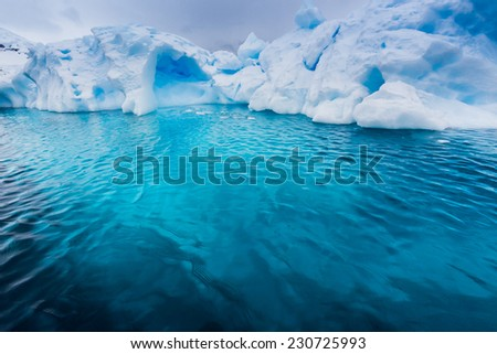 Turquoise color under an iceberg in Antarctica - stock photo
