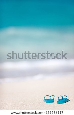 Turquoise flip flops on a tropical beach - stock photo