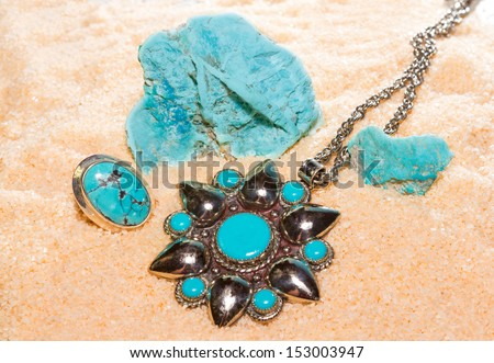 Turquoise gemstones with a pendant and ring with polished cabochons and a specimen of massive natural stone, used by ancient civilisations as a talisman - stock photo