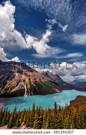 Turquoise glacial lake nestled between the mountain and pine trees, playful clouds in the sky - stock photo