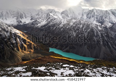 Turquoise highland alpine lake in deep rocky valley among snowcapped mountains under storm cloudy sky Altai Siberia Russia - stock photo