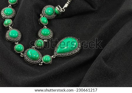 turquoise necklace on the black canvas - stock photo