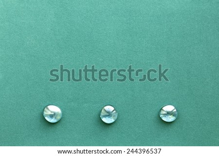 Turquoise rough paper background with three smooth glass pebbles - stock photo