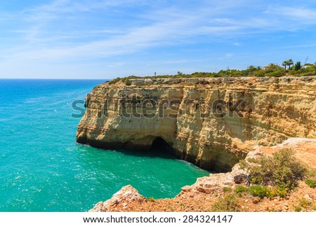Turquoise sea and cliff rocks on coast of Portugal near Carvoeiro town, Algarve region - stock photo