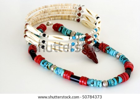 Turquoise, silver, bone, beads and coral crafted into exquisite Native American Traditional wear and photographed on plain background - stock photo