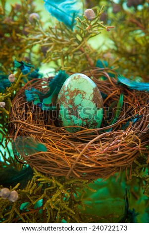 Turquoise stone Easter egg in a nest with feathers - stock photo