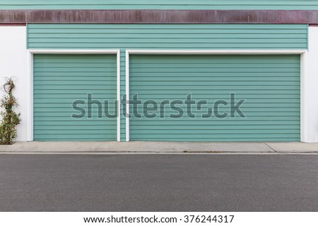 Turquoise three car garage door - stock photo