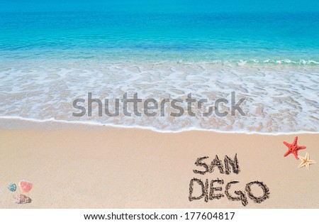 """turquoise water and golden sand with shells and sea stars with """"san diego"""" written on it - stock photo"""