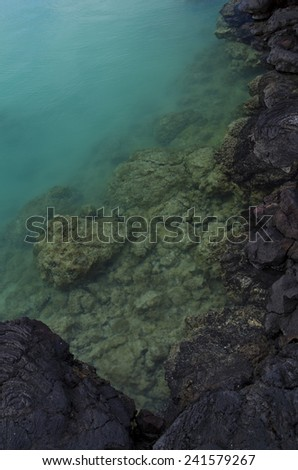 Turquoise water at lava rock shoreline - stock photo