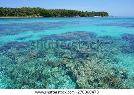 Turquoise water with coral reef below sea surface and a pristine tropical island in background, Caribbean, Cayos Zapatilla, Bocas del Toro, Panama - stock photo