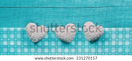 Turquoise wooden shabby chic background with white hearts on a checked frame, - stock photo