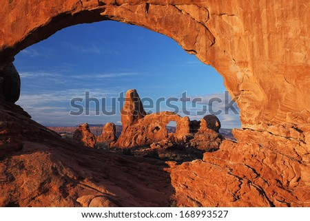 Turret Arch seen through the North Window Arch at sunrise in Arches National Park near Moab, Utah - stock photo
