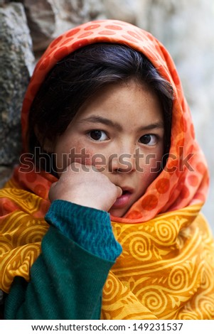 TURTUK, INDIA - JUNE 13: Balti shoolgirl Saanvi, 7, poses for a photo during her break time on June 13, 2012 in Turtuk Village, Ladakh, India. Turtuk village opened to foreign tourists in 2010. - stock photo