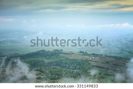 Tuscan country in morning mist with yellow skies, Val d'Orcia, Italy - stock photo
