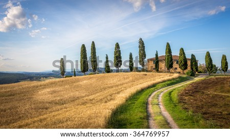 Tuscan landscape with farmhouse and cypress trees - stock photo