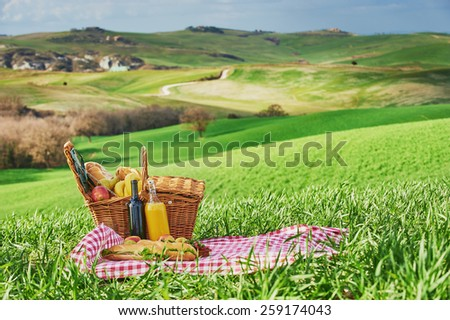 Tuscan picnic on the green spring grass with landscape in the background - stock photo