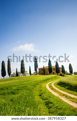 Tuscany, farmhouse with cypress trees, green meadow and blue sky - stock photo