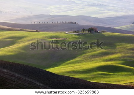Tuscany landscape at sunrise. Typical for the region tuscan farm house, green hills, vineyard. Italy - stock photo